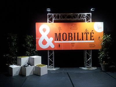 panneau orange mobilité, plantes et boites blanches autour