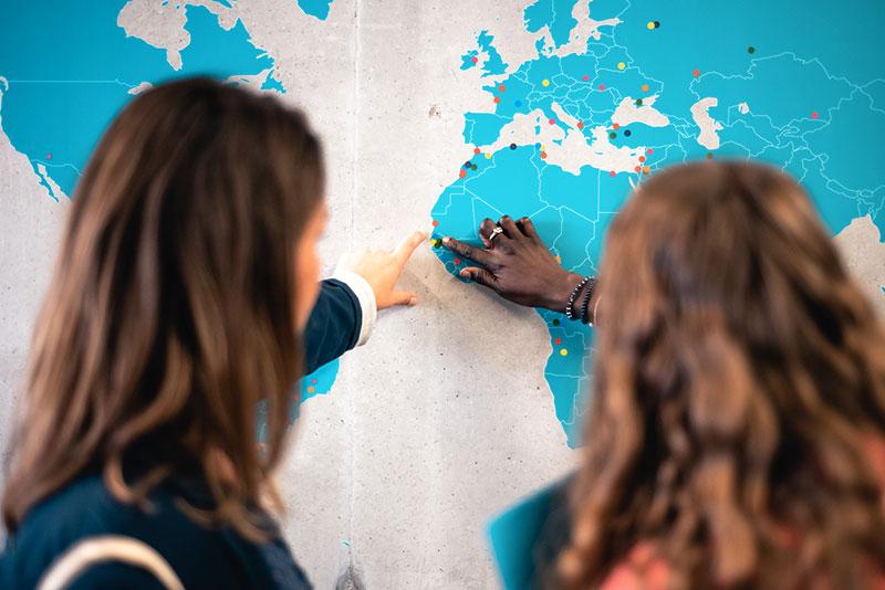 Etudiantes qui indiquent leur origine sur une carte du monde