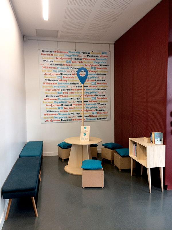 espace d'attente bleu, table avec picto, bancs et poufs bleus, petite bibliothèque