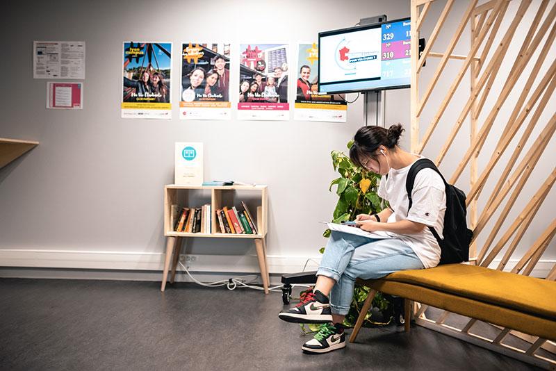 Etudiante qui rempli un dossier, paravent ajouré, écran d'information et petite meuble bibliothèque