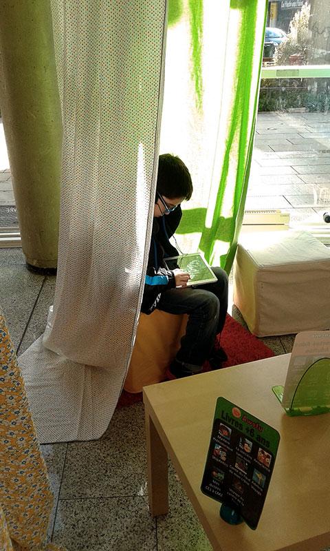 enfant qui lit dans une cabane en tissu