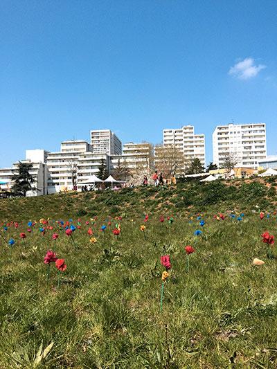 champ de fleurs en tissu dans une prairie devant des immeubles
