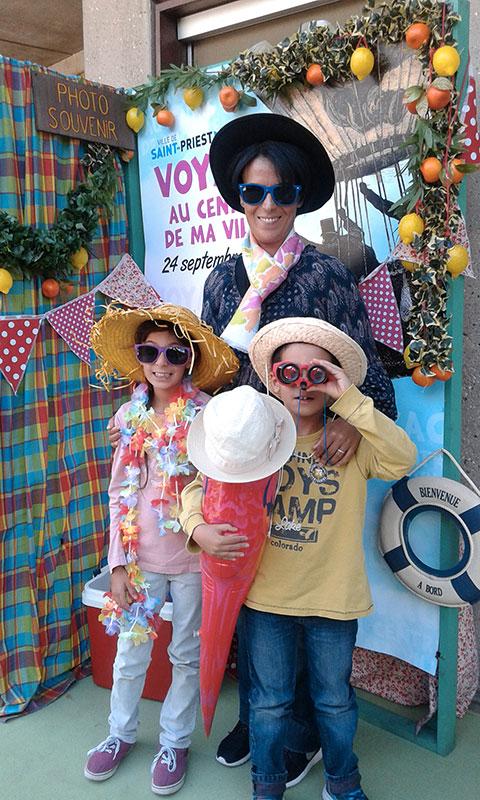 une dame et deux enfants dans un photobooth estival