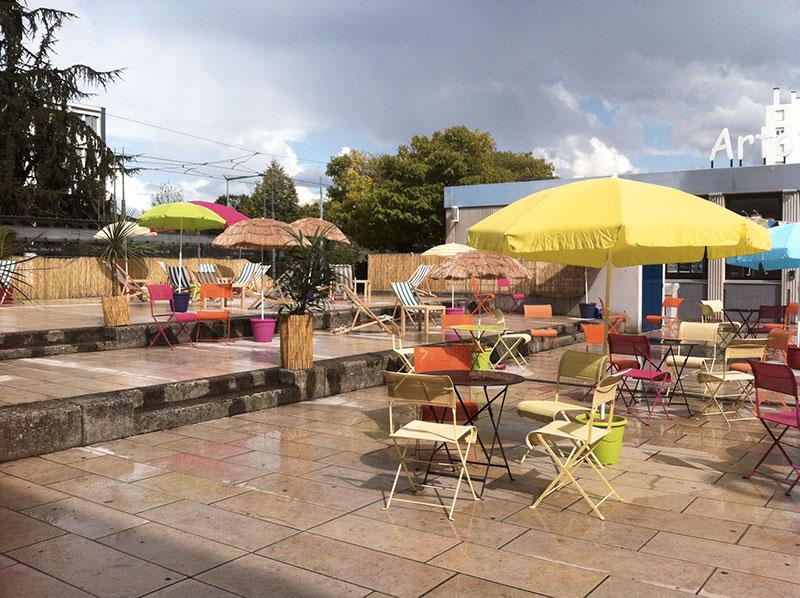 terrasse aménagée avec des transats, des parasols, des tables et des chaises