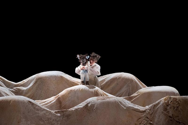 un personnage avec une marionnette dans un décor dunes de sable lors d'un spectacle pour enfants