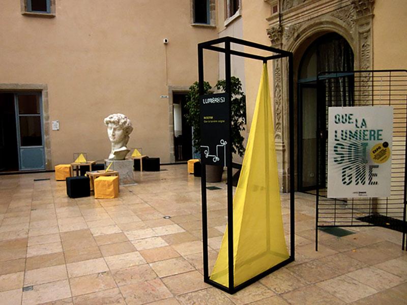Installations structures noires et cones jaunes servant de signalétique, coin repos au fond