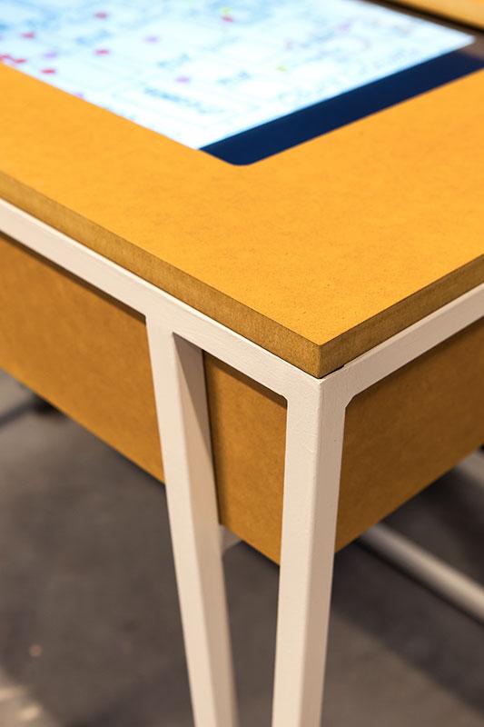 Gros plan sur table en valchromat jaune et acier blanc, tablette numerique insérée
