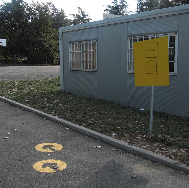Marquage sol flèches jaune et panneau de direction